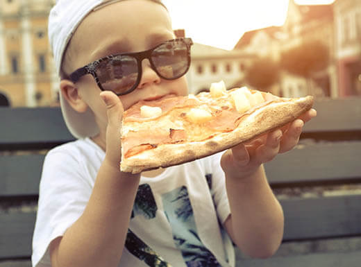 A child wearing sunglasses and a backwards ball cap eats pizza on a park bench in a neighborhood at sunset.