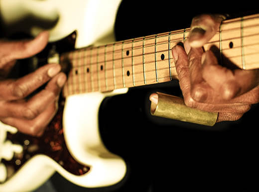 Close up view of man's hands playing guitar at National Blues Museum in St. Louis.