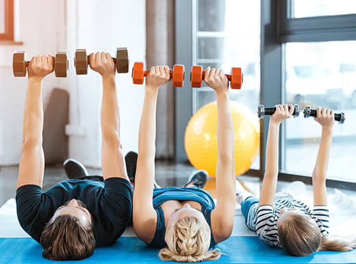 A mother, father, and young daughter exercise  with weights while laying on yoga mats inside their home on a bright morning