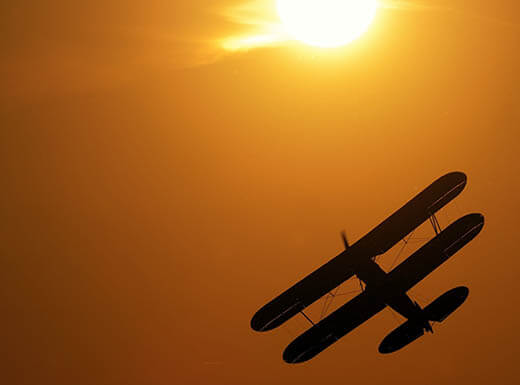 A silhouette of a vintage single-engine propeller biplane in Fort Myers, FL at sunset on a summer day.
