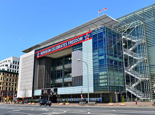 The glass and metal exterior of the Newseum building is pictured against a clear blue sky in Washington, D.C. on a bright afternoon with a red and blue sign reading Newseum Celebrates Freedom.