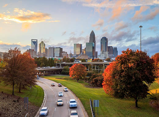 Aerial view of Charlotte, North Carolina skyline and roadway at sunset in autumn, showing trees with bright yellow, orange and red leaves in the foreground.