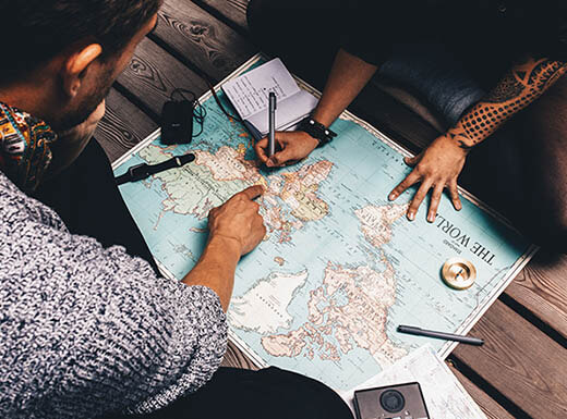 Two people sitting on the floor marking their roadtrip on a paper map