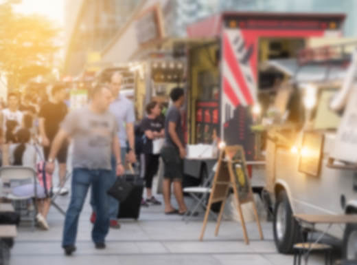 A blurred image of customers looking at a menu by a food truck in a downtown area on a bright evening as the sun sets around people eating food from the food trucks at small tables nearby