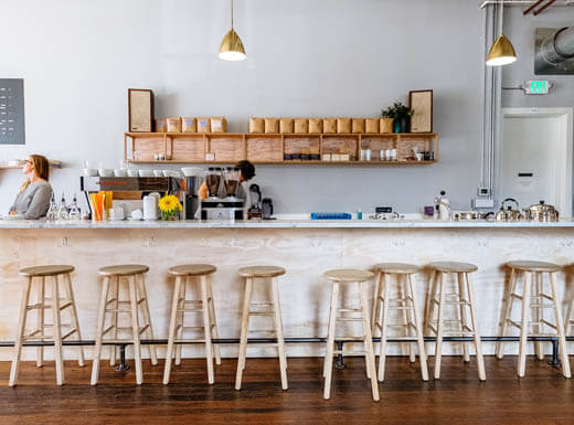Baristas working at Elm Coffee Roasters in Seattle, Washington, a clean, simple coffee bar with gold pendant lights above and simple wooden stools in front on a bright morning.