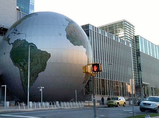 The Museum of Natural Sciences' modern glass building with a large globe structure is hit by the early morning sun in Raleigh, North Carolina.