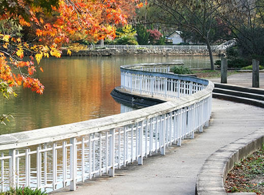 A white fence separates a paved path and a lake with orange, yellow and green leaves on the autumn trees at Pullen Park in Raleigh, North Carolina on a brisk morning.