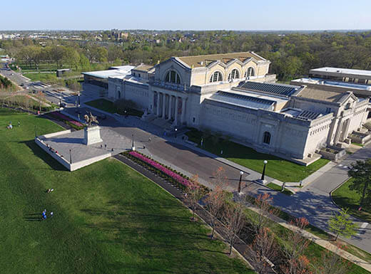 The grey concrete exterior of the St. Louis Art Museum is pictured from above, with bright green grass in front of it and trees in the background in St. Louis, Missouri on a bright afternoon