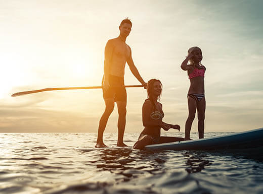 Mom, dad, and child enjoying paddle boarding in Fort Lauderdale as the sun sets.