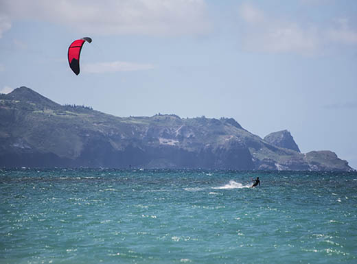 A kite surfer is spotted in the water at Kanaha Beach Park on a partly-cloudy afternoon.