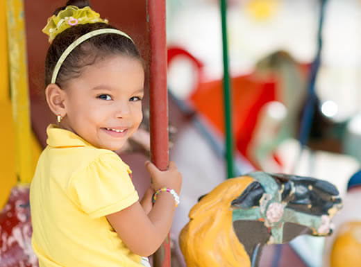 A cute young girl dressed in yellow smiles as she rides on a carousel on a bright afternoon.