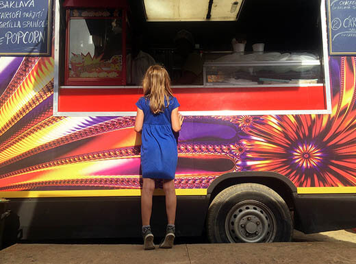 Little girl in a blue dress stands on her tip toes in front of colorful food truck on a sunny day in Detroit