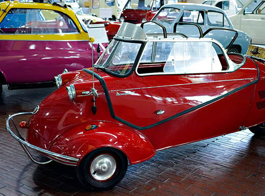 Lots of small colorful cars at Lane Motor Museum in Nashville are on display on a bright afternoon with the red 1957 Messerschmitt KR200 in the foreground.