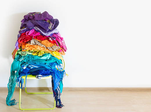 A pile of purple, pink, red, orange, yellow, blue, and green clothes sit stacked on top of a chair on a bright morning.