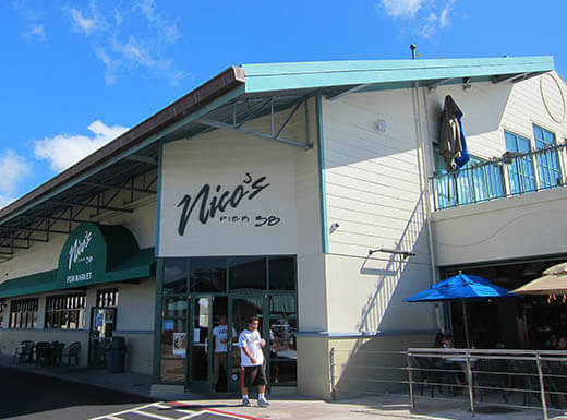 Outside view of Nico's seafood restaurant, with white exterior and a blue roof and trim on a clear sunny day in Honolulu, Hawaii