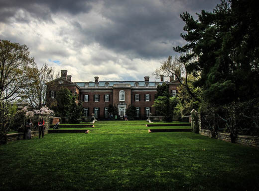 A dark and gloomy morning sky hovers over the bright green grass, stately brick building and tall trees in Dumbarton Oaks Gardens in Washington, D.C.