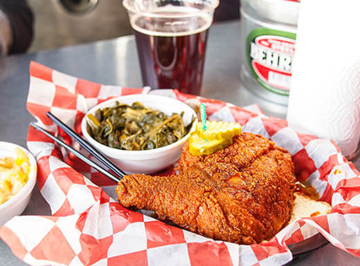 A serving basket with red and white checkered paper serves a fried chicken platter on top of a stainless-steel table on a bright afternoon in Nashville, TN.