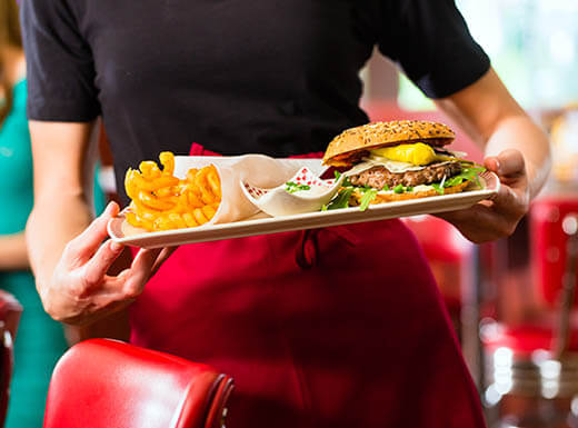 wearing a black shirt and red apron can be seen holding a tray with a large burger and fries on top of it on an early evening in Miami, Florida.