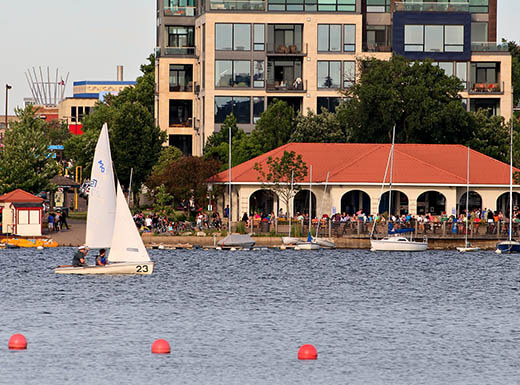 A view of the marina from the waters of Lake Calhoun in Minneapolis as a sailboat floats by on a clear morning.