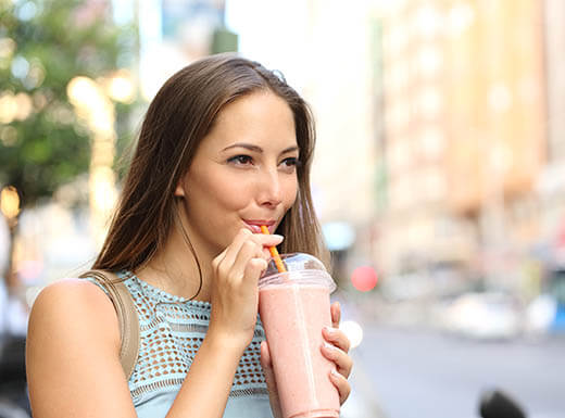 A woman enjoys a pink, fruit-filled smoothie that she got from a food truck on a sidewalk near a busy city street on an early morning.