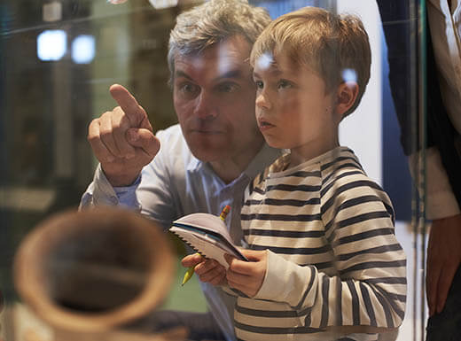 A father and son look at artifacts in a case at a Portland museum