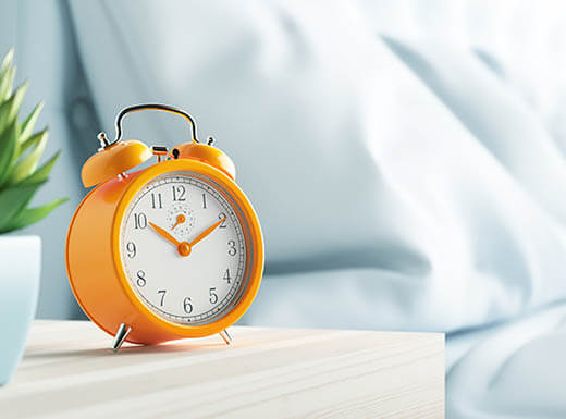 An orange clock sits next to a white bed in a San Francisco hotel room on a bright morning