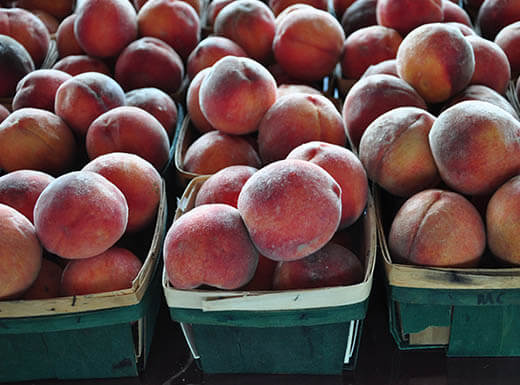 Piles of juicy red peaches sit in green wooden baskets waiting to be sold at the Historic City Market in Raleigh, North Carolina.