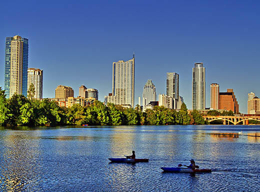 Two kayakers in Lady Bird Lake with the Austin, Texas, skyline behind them on a sunny day.