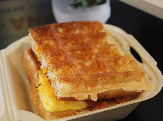 Close up view of a waffle sandwich in Styrofoam to-go box