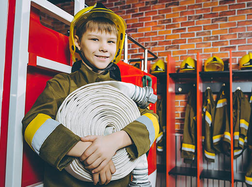 A young boy dressed in firefighter gear holds a rolled-up fire hose