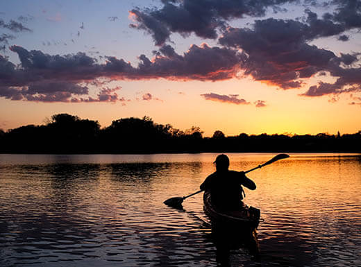 A kayaker paddles toward sunset on Lake of the Isles in Minneapolis on a crisp evening.