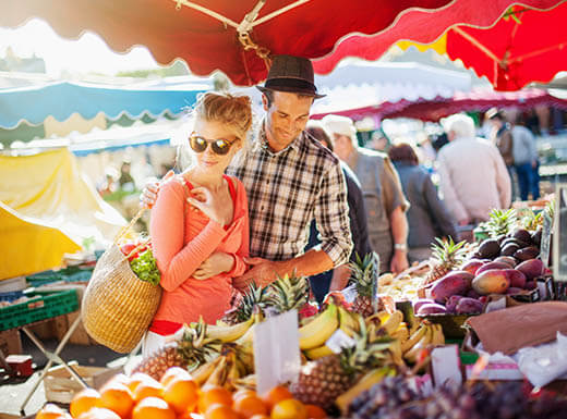 A young couple shops at a fresh fruit stand in an Orlando market on a bright morning.