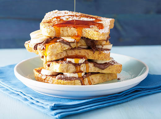 A caramel-covered stack of French toast and bananas sits high upon a white plate