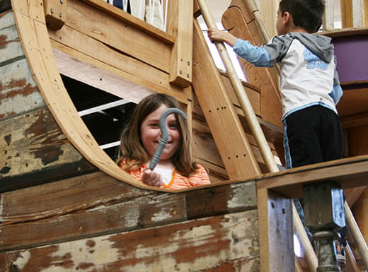 Kids climbing a wooden structure inside Marbles Kids Museum in Raleigh, NC.