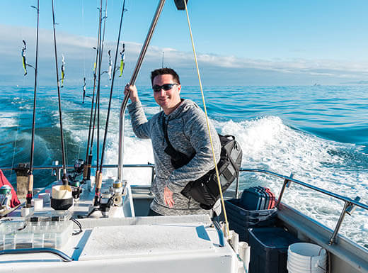 A man wears a hoodie and sunglasses on a fishing boat in Fort Myers, FL, on a sunny day