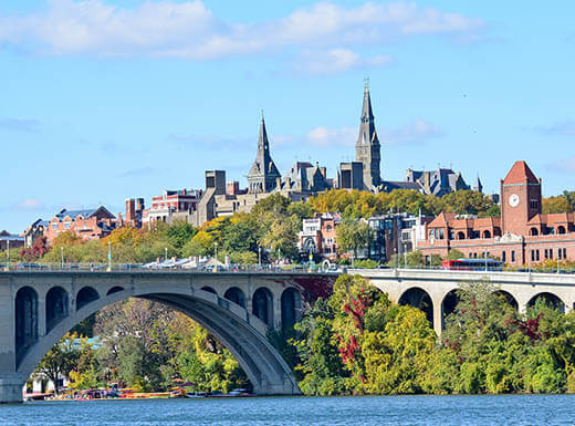 The Key Bridge is pictured in the foreground, with the skyline of Washington, D.C. in the background with gray spires and brick buildings against a light blue afternoon sky in autumn, as seen from the campus of Georgetown.