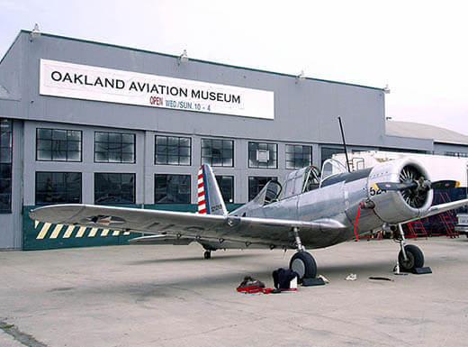 A small military plane is inspected by two men outside of Oakland Aviation Museum, a gray building with a sign out front, on a cloudy day.