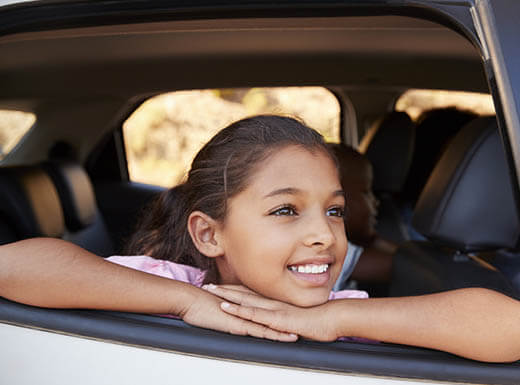 Young girl looks out the backseat window of a car