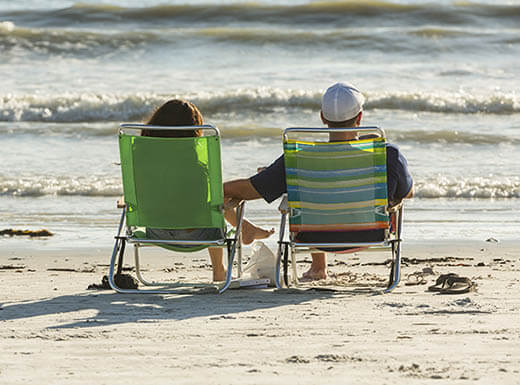 A man and woman are pictured on a white sandy beach from behind on green beach chairs, with the man's hand reaching over to the woman's lap and the ocean waves in the background on Fort Myers Beach, Little Hickory Island Beach Park, on the west coast of Florida