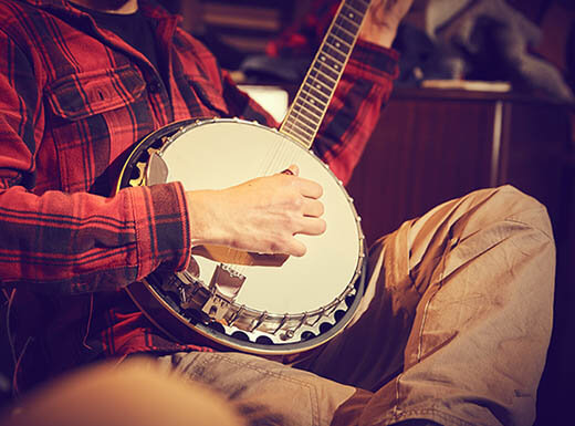 A close-up shot of a man in a red and black plaid shirt playing the banjo in Nashville, TN on an early evening.