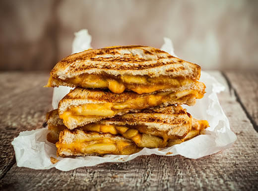 A gooey grilled cheese sandwich sits on top of crinkled parchment paper on a wooden table surface on a warm afternoon in a family-friendly restaurant in Miami, Florida