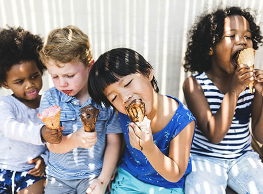 Four children enjoy ice cream cones in Fort Lauderdale, as light streams in on their faces from a window