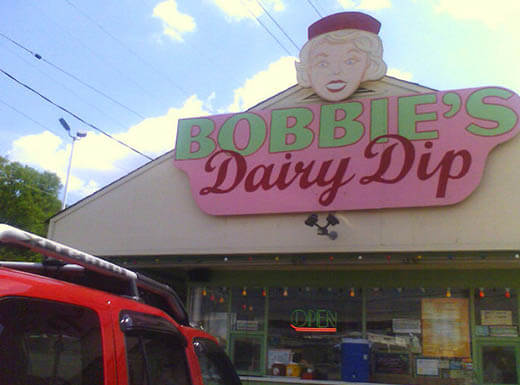 An external view of Bobbie's Dairy Dip restaurant in Nashville, Tennessee on a sunny day shows the pink and green sign with the face of a woman atop the bulding.