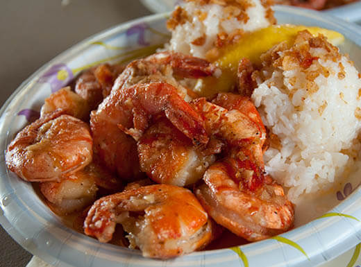 Freshly cooked plate of shrimp and rice on a paper plate at a Honolulu seafood restaurant in Hawaii