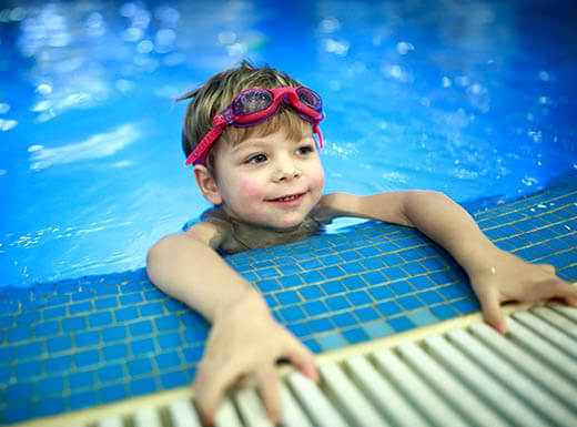 Young boy with goggles on his head holds on to the edge of a pool