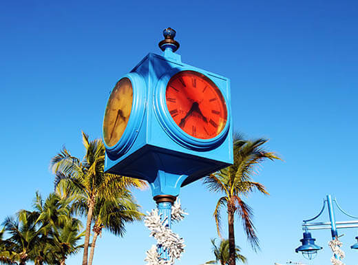The bright blue painted Times Square clock of Fort Myers is pictured with its red and yellow faces showing in downtown Fort Myers Beach, FL, with palm trees and a clear blue sky in the background