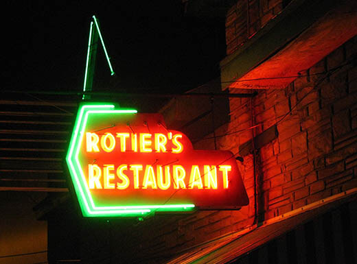 An external view of the neon Rotier's Restaurant sign, illuminated on a summer night.