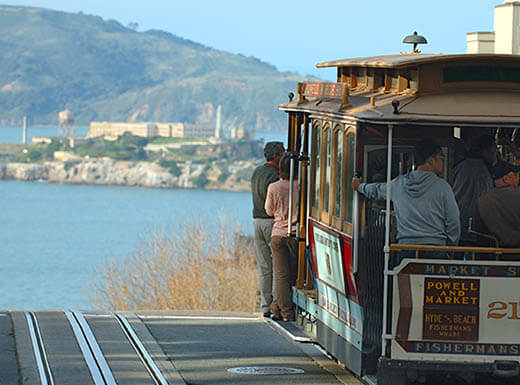 People stand and ride along in a San Francisco cable car on sunny afternoon.
