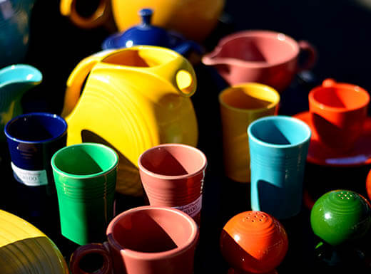 Colorful kitchenware, painted yellow, green, blue, pink and orange include pitchers, cups, saucers and salt and pepper shakers on display at a New Jersey flea market.