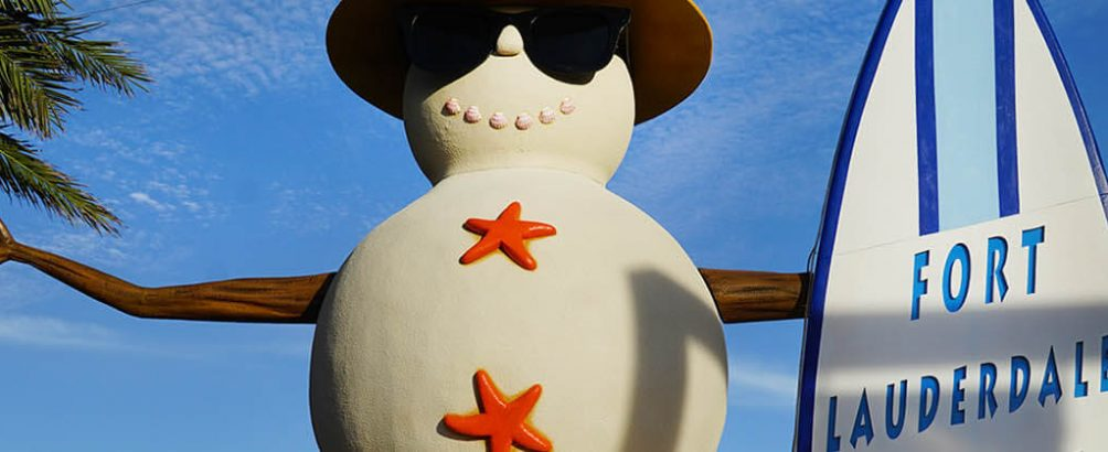 Snowman with starfish buttons and sunglasses next to surf board in sunny Fort Lauderdale